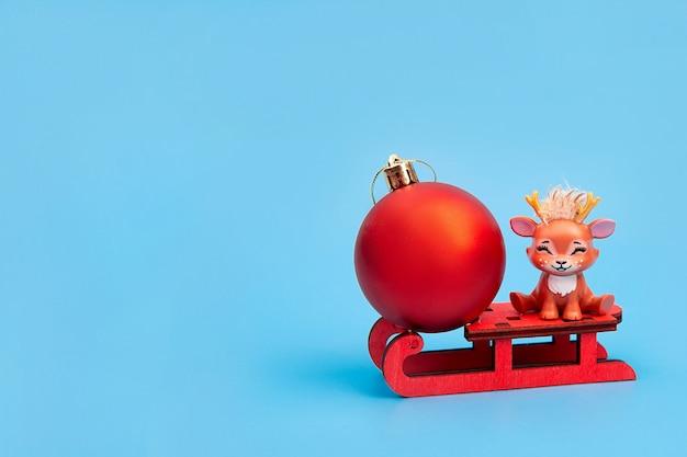 Leuke kerst rendieren met kerst rode bal zittend op een slee. concept van kerstmis, gelukkig nieuwjaar. ansichtkaart.