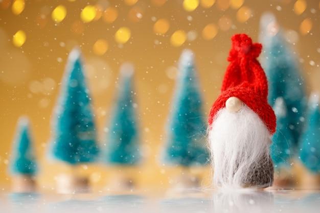 Leuke kerstkabouter zit en wacht op zijn cadeautjes voor kerstmis op gele bokeh achtergrond.