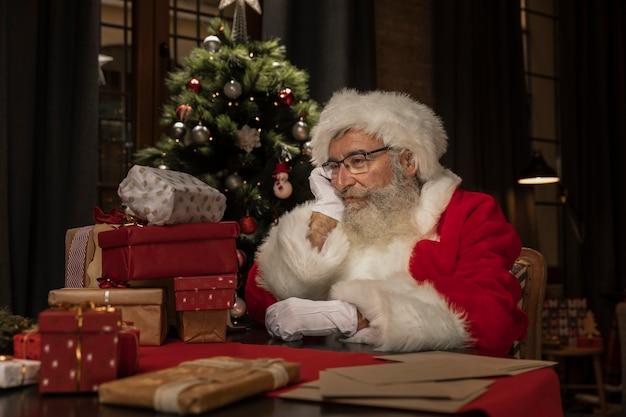 Leuke kerstman aan tafel denken