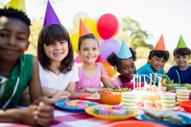 Leuke kinderen die en tijdens een verjaardagspartij glimlachen stellen