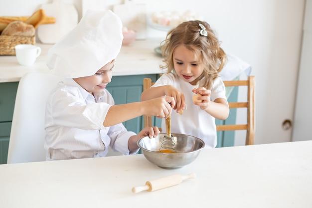 Leuke kinderen die in de keuken genieten van bereiden voedsel voor