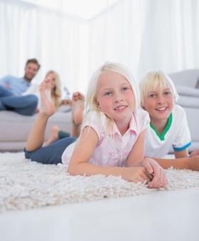 Leuke kinderen die op het tapijt liggen die bij camera glimlachen