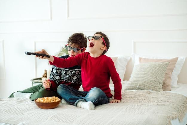 Leuke kinderen die popcorn eten terwijl ze thuis tv kijken in 3 d-glazen.