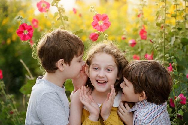 Leuke kinderen fluisteren in de zomer buiten.