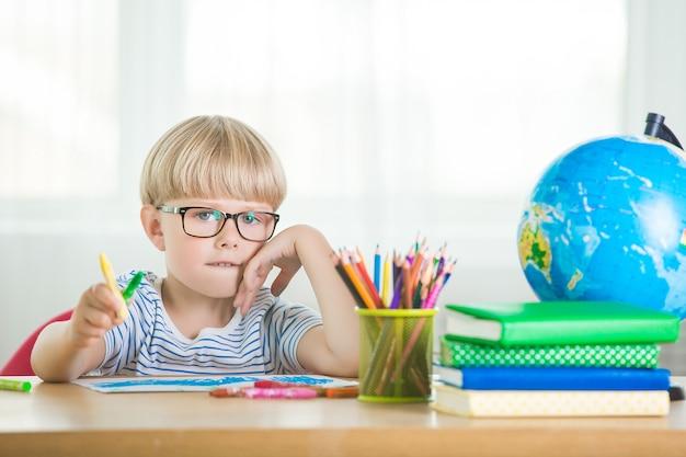 Leuke kinderstudie thuis. kleine jongen met globe en boeken binnenshuis. schattig student leren lessen en taken uitvoeren