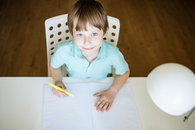 Leuke kindjongen die huiswerk doet. slimme jongen tekenen aan balie. schooljongen. basisschoolstudent tekenen op werkplek. kind geniet van leren. thuisonderwijs. terug naar school. mockup-afbeelding