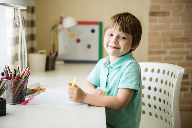 Leuke kindjongen die huiswerk doet. slimme jongen tekenen aan balie. schooljongen. basisschoolstudent tekenen op werkplek. kind geniet van leren. thuisonderwijs. terug naar school