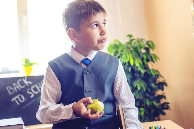 Leuke kindzitting bij het bureau in het klaslokaal. jongen die apple op een schoolpauze eet