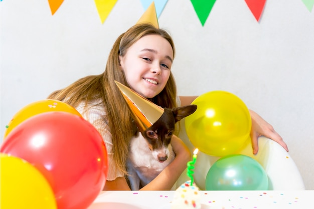 Leuke kleine grappige hond met een verjaardagstaart en een feestmuts die verjaardag viert