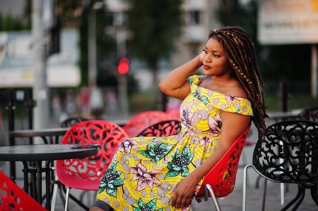 Leuke kleine hoogte vrouw met dreadlocks, dragen op gekleurde gele jurk, zittend op terras op rode stoel