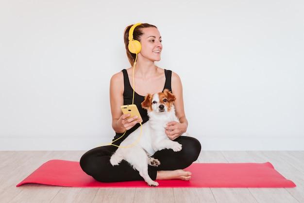 Leuke kleine jack russell hond die yoga op een mat thuis met haar eigenaar doet. jonge vrouw die aan muziek op gele mobiele telefoon en hoofdtelefoon luistert. gezonde levensstijl binnen
