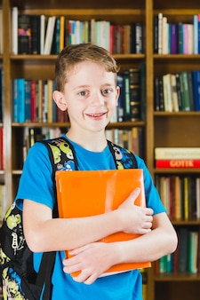 Leuke kleine jongen die zich in bibliotheek bevindt