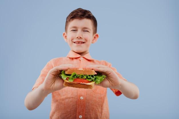 Leuke kleine jongen met boterham in de hand kijkt naar de camera geïsoleerd op blauwe achtergrond kopie ruimte