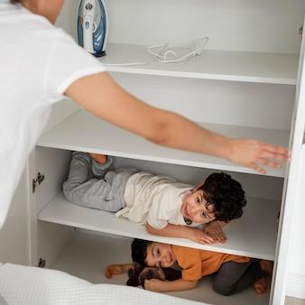 Leuke kleine jongens die zich verstoppen in de kleerkast