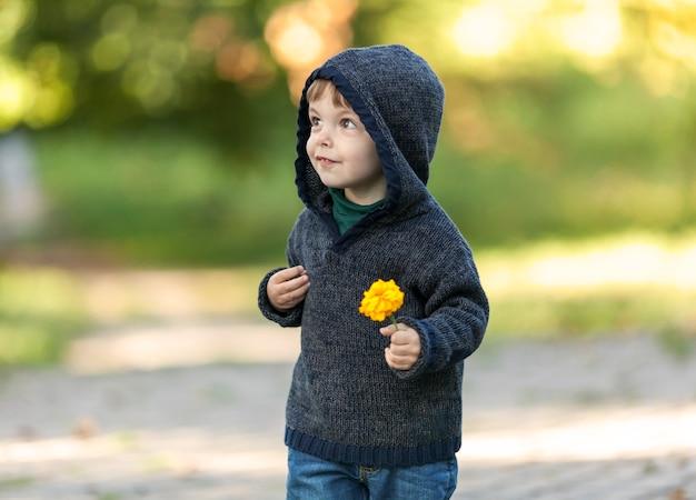 Leuke kleine kerel die in het park met een bloem loopt