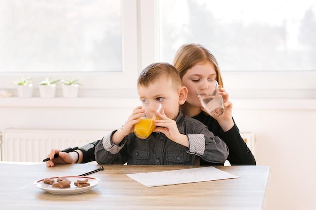 Leuke kleine kinderen die water en sap thuis of op kinderdagverblijf drinken