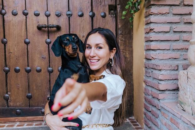 Leuke kleine worsthondzitting in openlucht met haar eigenaar thuis. vrouw die haar hond knuffelt. liefde voor dieren concept