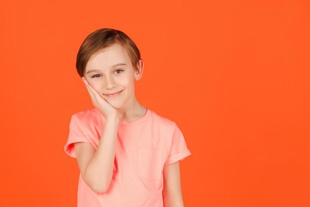 Leuke knappe glimlachende preteen jongen die zich voordeed in de studio. portret van een vrolijke jongen. kind gekleed in casual kleurrijke tshirt schoonheid, zomer, mode. verbaasd en opgetogen schoolkind.