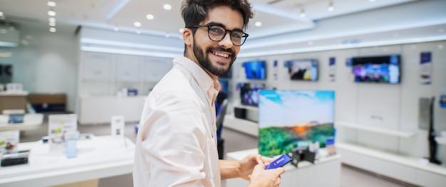 Leuke knappe jonge man die in heldere elektronische winkel. enkele nieuwe telefoons testen.