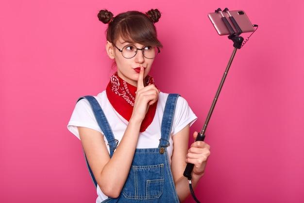 Leuke knappe jonge vrouw met een doordachte uitdrukking, nadelen mond met de vinger, houdt geheim, wordt gefotografeerd door zichzelf, geïsoleerd op roze. tieners concept