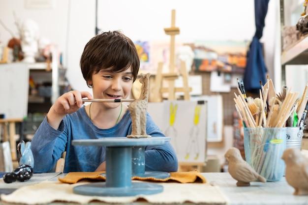 Leuke knappe jongen die kleidier in kunstacademie beeldhouwen