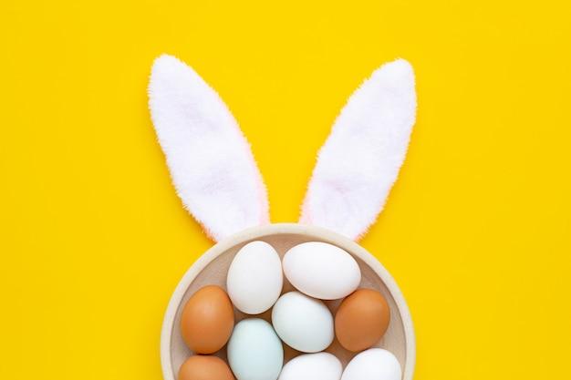 Leuke konijntjesoren met eieren op gele achtergrond. pasen