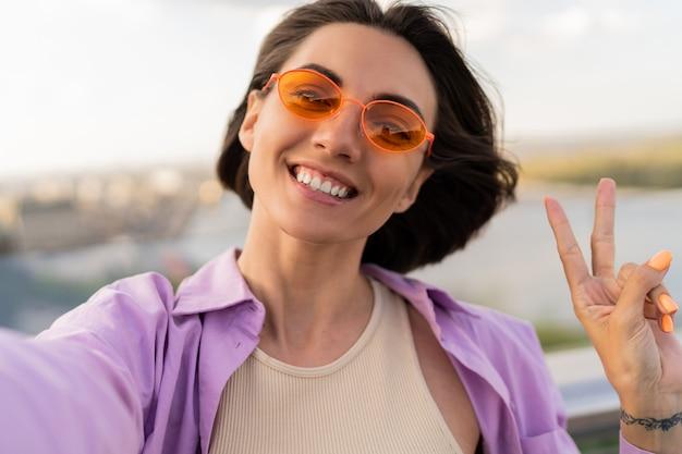 Leuke kortharige vrouw die in oranje zonnebril zelfportret op de brug maakt