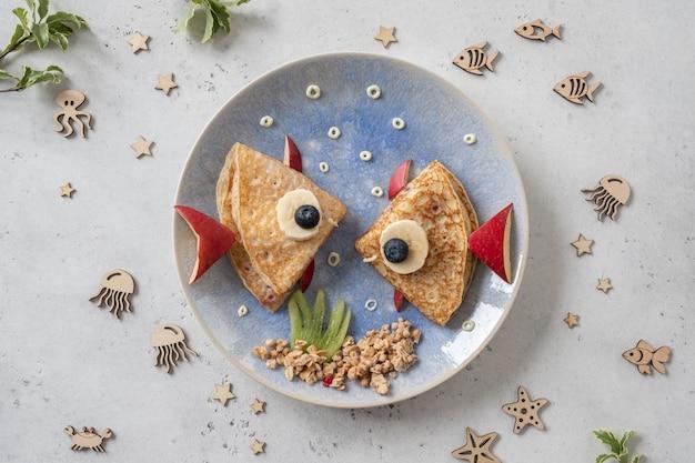 Leuke krab- en kreeftcroissants met fruit voor het ontbijt voor kinderen