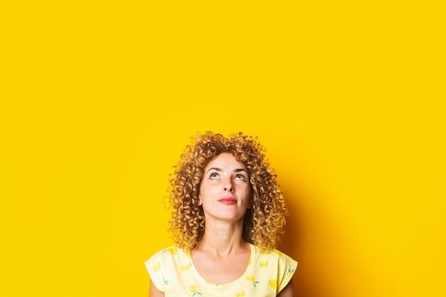 Leuke krullende jonge vrouw kijkt peinzend omhoog op een gele achtergrond