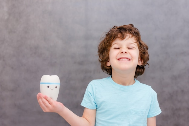 Leuke krullende jongen houdt grote tand en glimlach op grijze muur. het concept van de gezondheid van kinderen, medicijnen.