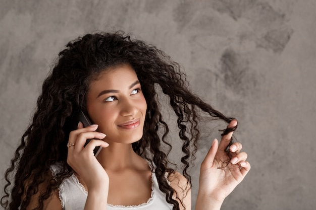 Leuke krullende vrouw die op telefoon spreekt, rolt haar streng op vinger