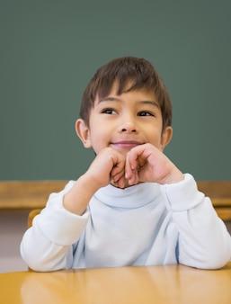 Leuke leerling die bij bureau in klaslokaal denkt