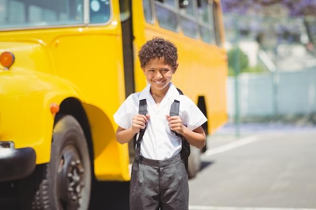 Leuke leerling die bij camera door de schoolbus glimlacht