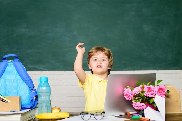Leuke leerling die huiswerk maakt heeft een goed idee schooljongen met laptop heeft een nieuw idee basisschool