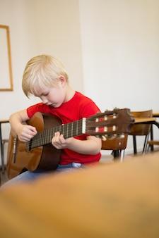 Leuke leerling gitaarspelen in de klas