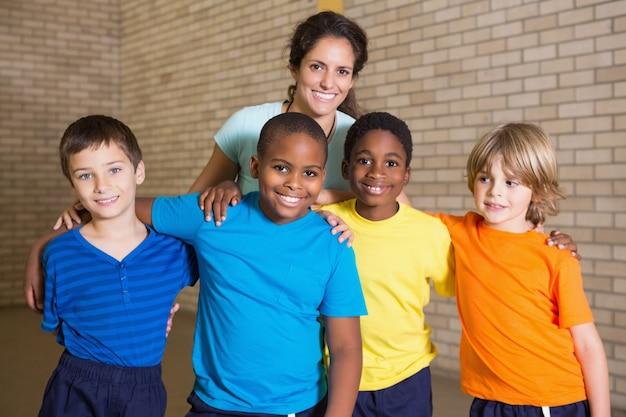 Leuke leerlingen die bij camera met pe leraar glimlachen op de basisschool