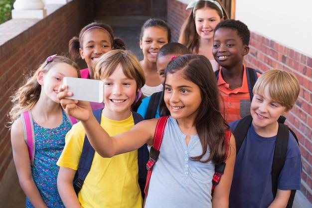 Leuke leerlingen die mobiele telefoon met behulp van