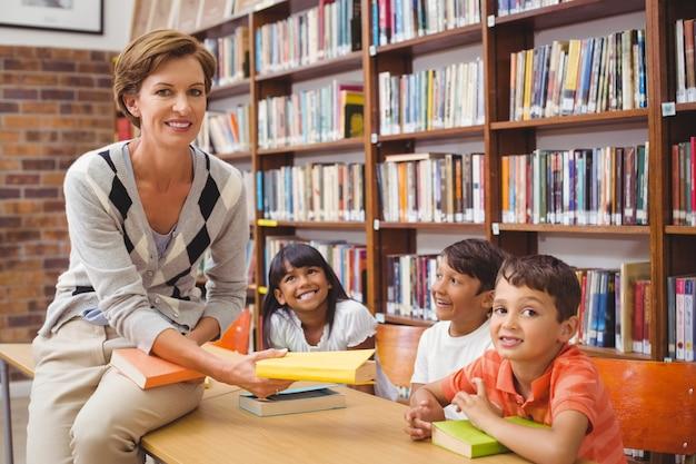 Leuke leerlingen en leraar die boeken in bibliotheek zoeken