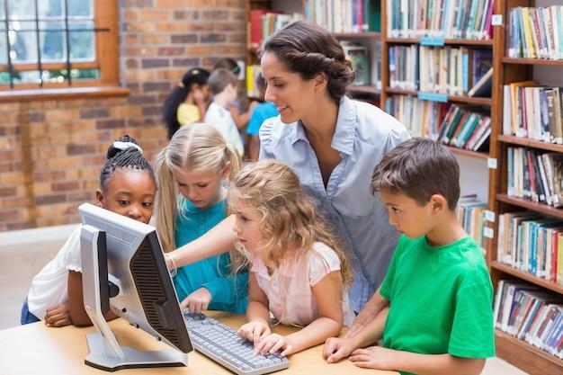 Leuke leerlingen en leraar die computer in bibliotheek bekijken