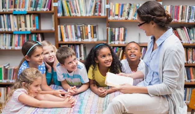 Leuke leerlingen en leraar die in bibliotheek lezen