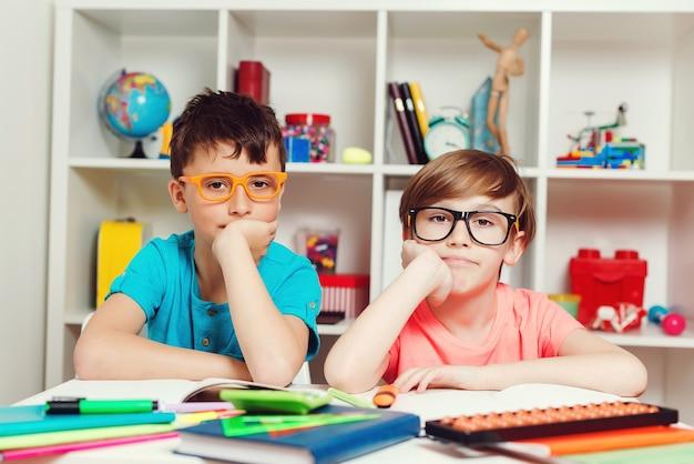 Leuke leerlingen in de klas op de basisschool. terug naar schoolconcept. portret van twee slimme jongens op de werkplek in de klas. onderwijs, leren en mensen concept.