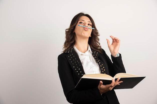 Leuke leraar die pen op haar mond houdt.