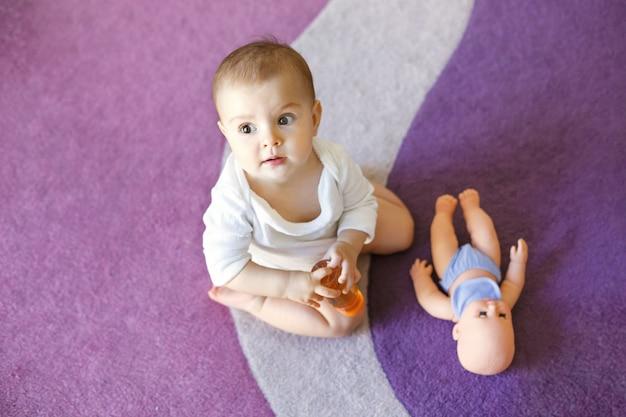 Leuke leuke kleine babyvrouw zittend op paars tapijt met pop.