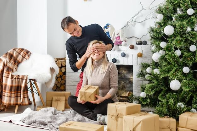 Leuke liefde paar zittend op tapijt voor open haard. vrouw en man vieren kerstmis