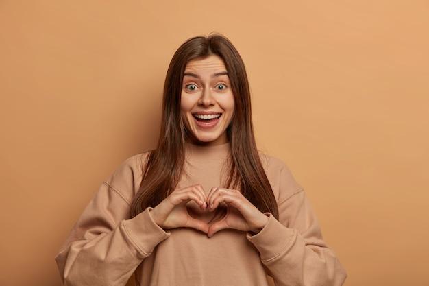 Leuke liefdevolle vrouw drukt passie, genegenheid en romantische stemming uit naar vriend, vormt hartgebaar, verspreidt liefde en glimlacht graag