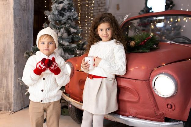 Leuke lieve kinderen in de buurt van rode auto en kerstboom en verlichting