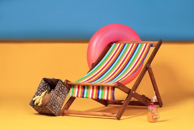 Leuke ligstoel op geïmproviseerd kunstmatig strand, compleet met opblaasbare cirkel en doos met tropisch fruit