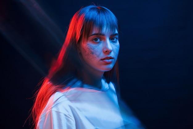 Leuke make-up. studio opname in donkere studio met neonlicht. portret van een jong meisje