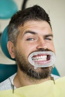 Leuke man die lacht camera kijken. portret van vrolijke mannelijke persoon met sneeuwwitte tanden. senior man