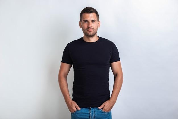 Leuke man draagt in zwart t-shirt staat met zijn armen in de zak, serieus te kijken naar de camera